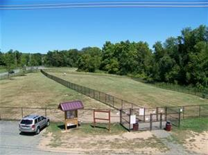 Aerial image of fenced in field, with a car in a parking lot